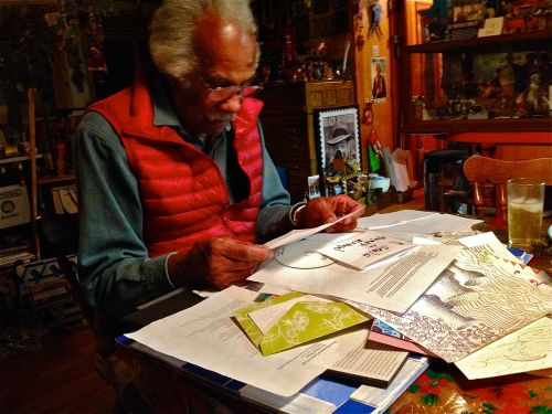"""Islesford artist Ashley Bryan goes through reams of appreciative letters generated by his exhibit, """"A Visit With Ashley Bryan,"""" currently on display at the Ethel H. Blum Gallery at College of the Atlantic."""