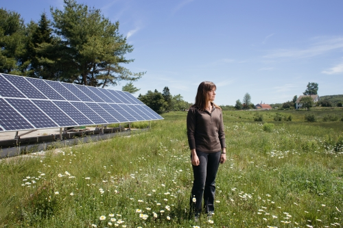 Saren Peetz, 22, and a recent graduate of College of Atlantic in Bar Harbor, stands for a portrait in front of an array of solar panels on the Peggy Rockefeller Farms on Mount Desert Island, Maine, on Wednesday, June 17, 2015. Peetz, who graduated this year with a BA in Human Ecology, will spend the summer on Mount Desert Island, home to College of the Atlantic (COA), the town of Bar Harbor and Acadia National Park, as a COA Energy Fellow, where she will work to expand the solar array to serve the energy needs of the farm and surrounding community. The growing number of solar arrays, along with providing energy audits and housing upgrades, is part of the College of the Atlantic's larger mission  to tangibly link classroom curriculum that advances sustainable living practices with the surrounding communities on Mount Desert Island.